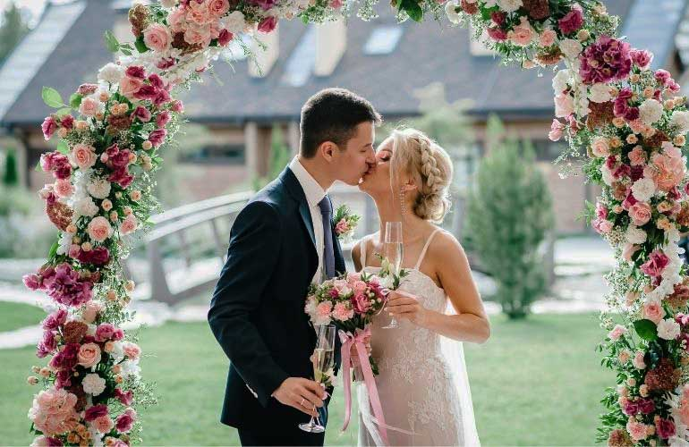 Bride and groom kissing under flower arch at a Long Island  micro wedding.