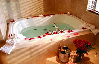 Bathtub surrounded by rose petals and an ice bucket with champagne.