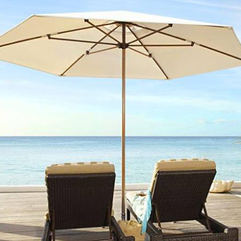2 Lounge chairs with umbrella overlooking the ocean.