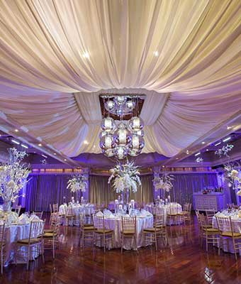 White table setup in ballroom with purple uplighting.