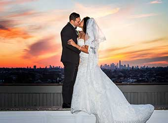Bride and Groom Kissing with NYC Skyline in Background Terrace on The Park