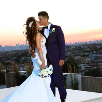 Bride and groom kiss under a sunset with the city landscape in the background.