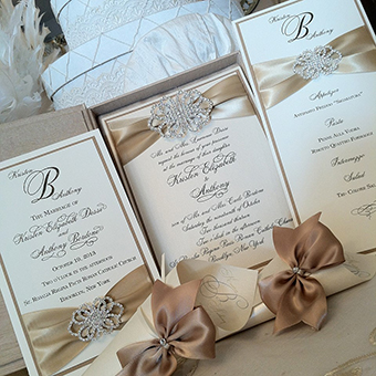 Close up of multiple invitations with tan ribbon and brooch in the center.