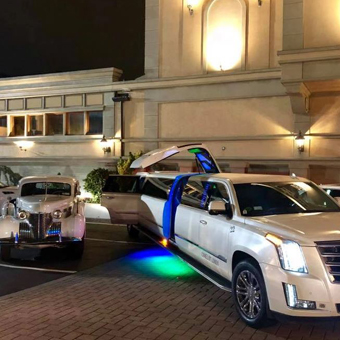 Vintage car and a limousine in front of a venue.