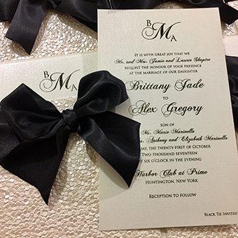 Invitation with black text alongside a black ribbon.