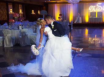 Groom Dipping Bride on Dance Floor with White Bouquet at Russo's