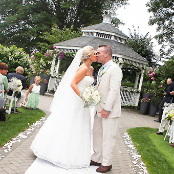 Couple kissing at outdoor ceremony in front of gazebo.