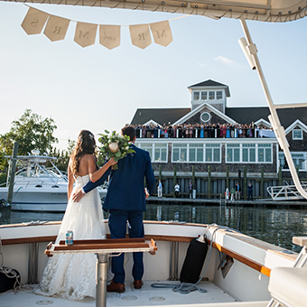 Bride and groom pose on a boat looking towards the wedding party at the venue.