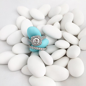 Handful of white Jordan almonds with an engagement and wedding ring encircling two blue Jordan almon