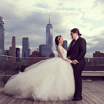 Bride and Groom posing holding hands and looking at each other with NYC in background.