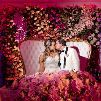 Bride and Groom sitting on white couch kissing with flower wall backdrop.