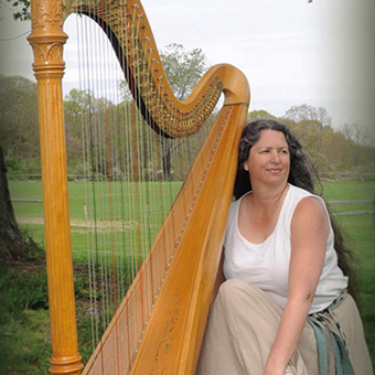 Janet King poses with her harp.