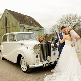 Bride and groom kiss in front of a Rolls Royce Silver Wraith.