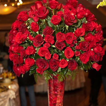 Red roses  in a tall vase centerpiece.